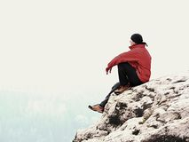 Man tourist  sit on exposed rock summit.  View point  above mist.  Sad man watching over autumnal valley Royalty Free Stock Photo