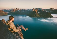 Man tourist sitting alone on the edge cliff mountains above sea. Travel adventure lifestyle extreme vacations in Norway stock image