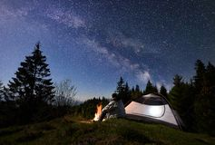 Male hiker enjoyng night camping near tourist tent at campfire under blue starry sky and Milky way. Man tourist sitting alone near illuminated tent at burning stock image
