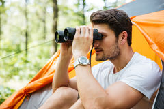 Man tourist sitting and looking at binoculars in forest Stock Images