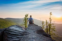 Man tourist sitting on top of hill at sunrise Royalty Free Stock Photos