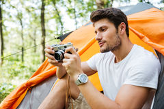 Man tourist sitting and using old vintage camera in forest Stock Image