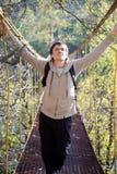Man tourist on a suspension bridge enjoys  evening Stock Image
