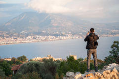Man tourist taking photos of a city from the high point Stock Images