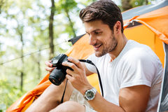Man tourist taking photos with modern photo camera in forest. Cheerful young man tourist sitting and taking photos with modern photo camera in forest Stock Photo
