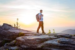Man tourist on top of hill at sunrise. Royalty Free Stock Photos