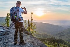 Man tourist on top of hill taking photo of sunrise Royalty Free Stock Images