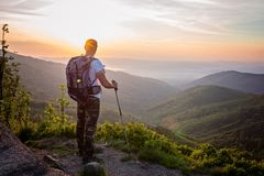 Man tourist with trekking poles on top of hill at sunrise Royalty Free Stock Image