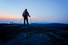 Man tourist with trekking on top of hill Royalty Free Stock Images