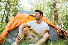 Man tourist using smartphone sitting in touristic tent at forest Royalty Free Stock Photo