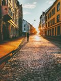 Man tourist walking in sunset street. Travel Lifestyle concept vacations cobblestone road Alesund city in Norway Stock Photography