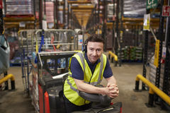 Man on tow tractor in distribution warehouse leans to camera royalty free stock photos