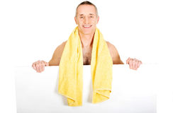 Man with towel around neck holding empty banner Stock Images