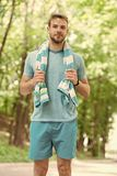 Man with towel on natural landscape. Sportsman just after training. Sweaty and tired. Summer beach time and vacation royalty free stock photos