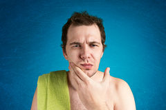 Man with a towel on shoulder. Is thinking about shaving Royalty Free Stock Photography