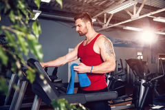 Man with a towel beside a treadmill Royalty Free Stock Photo