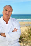 Man in a toweling robe by the sea Royalty Free Stock Photography