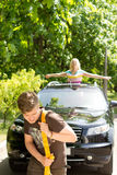 Man towing a car after a breakdown. Pulling it along behind him on a strap while being cheered on by his girlfriend or wife Stock Images