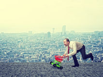 Man with toy trolley. And urban background Stock Image
