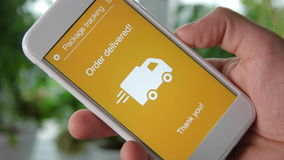Man tracks his package using smartphone application. Order delivered. Using app on the smartphone stock footage
