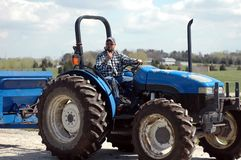 Man on tractor. Mexican-American man driving tractor at horse farm royalty free stock image