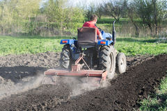Man on the tractor, back view. A man cultivates a garden, a view from behind Royalty Free Stock Image