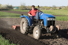 Man on the tractor in the field. Tractor with a lowered cutter in the garden Stock Image
