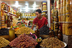 Man trades a green olives in a market Marrakesh, Morocco. Unknown man trades a green olives in a market (souk), August 07, 2015 in a Marrakesh, Morocco. The Stock Images