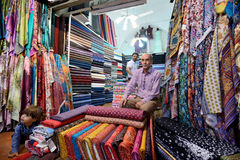 Man trades traditional iranian fabrics Stock Photo