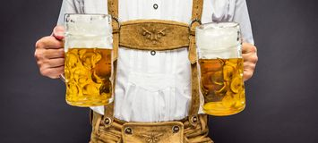 Man in traditional bavarian clothes holding mug of beer stock images