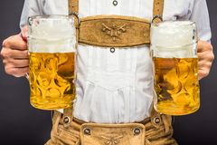 Man in traditional bavarian clothes holding mug of beer stock photo