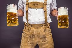 Man in traditional bavarian clothes holding mug of beer royalty free stock photo