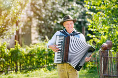 Man in traditional bavarian clothes playing the accordion. Man in traditional bavarian clothes standing in the garden in front of wooden fence, playing accordion stock photos