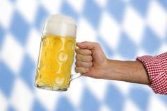 Man in traditional Bavarian shirt holds mug of beer Royalty Free Stock Photo