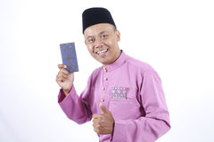 Man in traditional clothing cheerful with money packet during celebrate Eid Fitr Royalty Free Stock Photography