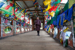 Man in traditional dress stands between prayer flags on bridge i Royalty Free Stock Images
