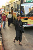 Man in traditional dress walking on the busy streets of Yangon, Royalty Free Stock Photo