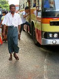 Man in traditional dress walking on the busy streets of Yangon, Stock Image