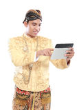 Man with traditional java suit using tablet PC Royalty Free Stock Image