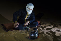 Man in traditional Tuareg outfit making tea in a desert. At night stock images