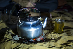 Man in traditional Tuareg outfit making tea in a desert. At night royalty free stock photography