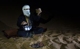 Man in traditional Tuareg outfit making tea in a desert. At night stock photos