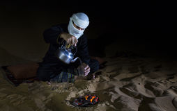 Man in traditional Tuareg outfit making tea in a desert. At night royalty free stock image