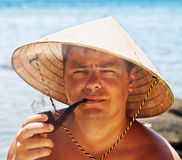 Man in a traditional Vietnamese hat smoking a pipe Stock Images