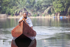 Man in traditional, wooden boat on african river Stock Image