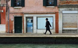 Man in traditonal  Jewish Suit  walking along canal side near the Jewish getto in Venice. Royalty Free Stock Image