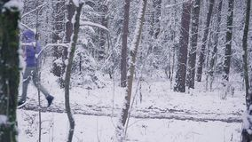 Man trail runner running in winter forest. Inspiration and motivation concept outdoors. Cross country running person on snow in forest. Sport and fitness in stock video footage