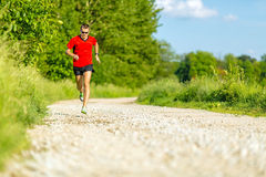 Man trail running on country road Stock Images