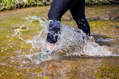 Man trail running in the mountain. Crossing a creek Royalty Free Stock Photo
