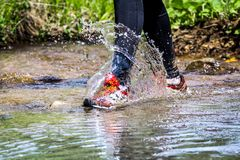 Man trail running in the mountain. S, crossing a creek Royalty Free Stock Photos